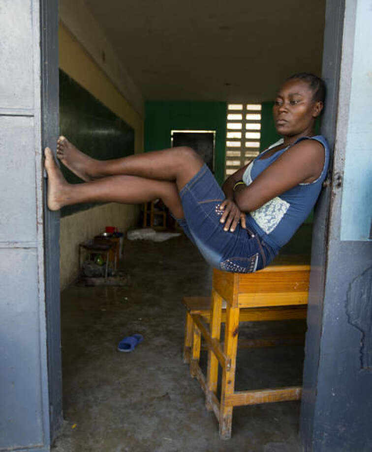 "Alexis Aniese, 36, sits in the entrance of a classroom at the Dumersais Estime public school where she's taken refuge after losing her home to Hurricane Matthew in Les Cayes, Haiti, Monday, Oct. 17, 2016. ""I want them to start classes, but at the same time, we need someplace new to live. We don't have the ability to make that happen on our own,"" she said. (AP Photo/Dieu Nalio Chery)"