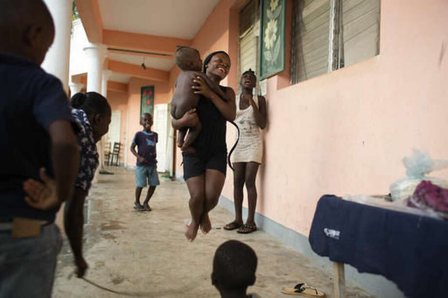 A youth jumps rope, while holding a baby, at a school where people have taken refuge after losing their homes to Hurricane Matthew in the village of Mersan, located in Camp-Perrin, a district of Les Cayes, Haiti, Sunday, Oct. 16, 2016. Aid workers who specialize in working with children in crisis say they fear kids will struggle with emotional aftershocks of the violent storm. (AP Photo/Dieu Nalio Chery)