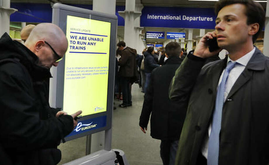 Travelers wait at St Pancras International train station in London, as Eurotunnel trains were suspended on Tuesday, Oct. 18, 2016. An electrical supply problem in the train tunnel beneath the English Channel has blocked Eurostar traffic between Britain and the European continent. (AP Photo/Frank Augstein)