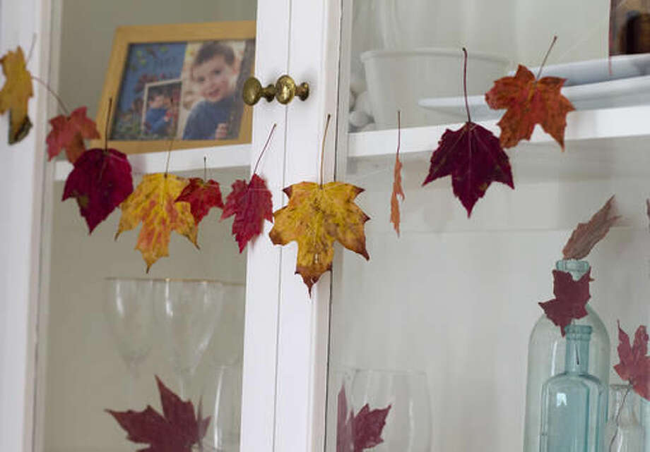 This Oct. 15, 2016 photo shows a variety of leaves strung together and hung as a decorative garland in Hopkinton, N.H. Extend the beauty of fall by preserving autumn leaves and turning them into decorations. (AP Photo/Holly Ramer)