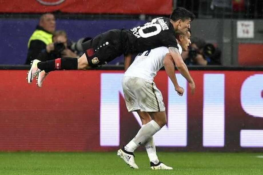 Leverkusen's Charles Aranguiz jumps over Tottenham's Erik Lamela during the Champions League group E soccer match between Bayer Leverkusen and Tottenham Hotspur in Leverkusen, Germany, Tuesday, Oct. 18, 2016. (AP Photo/Martin Meissner)