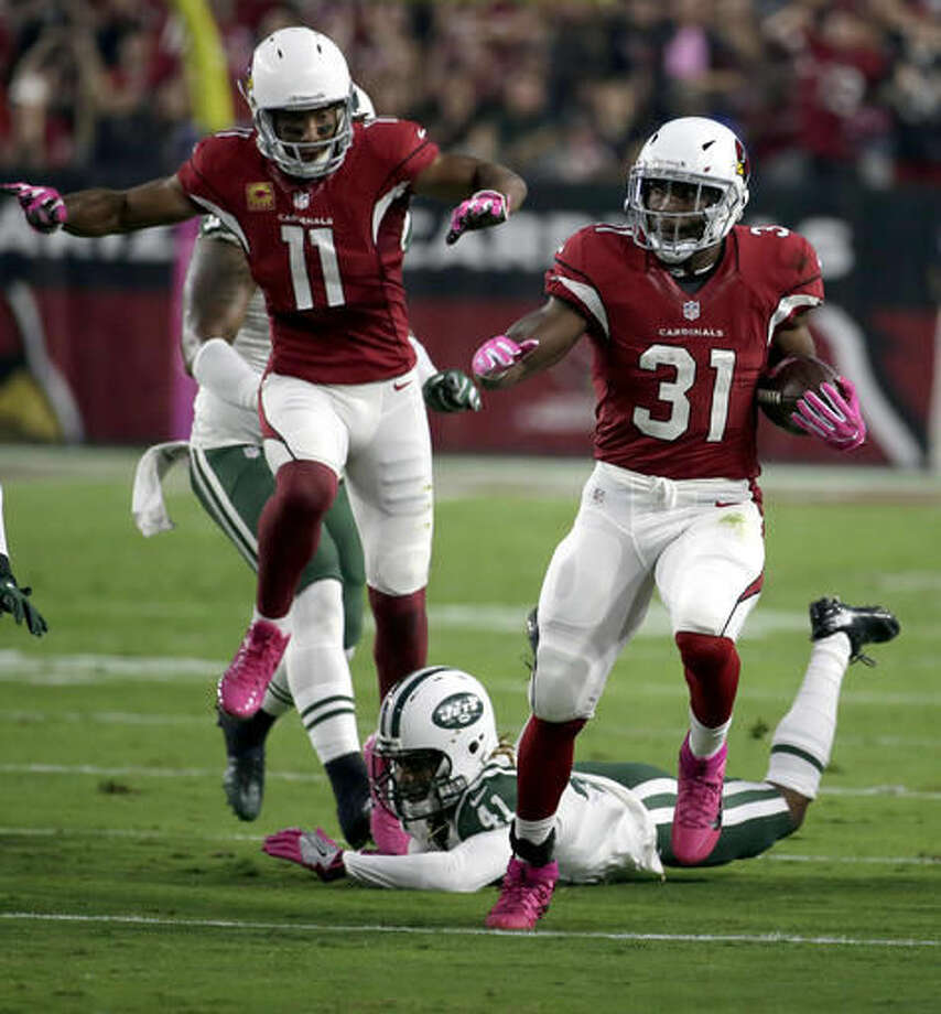Arizona Cardinals running back David Johnson (31) runs for a touchdown against the New York Jets as teammate Larry Fitzgerald (11) follows during the first half of an NFL football game, Monday, Oct. 17, 2016, in Glendale, Ariz. (AP Photo/Rick Scuteri)