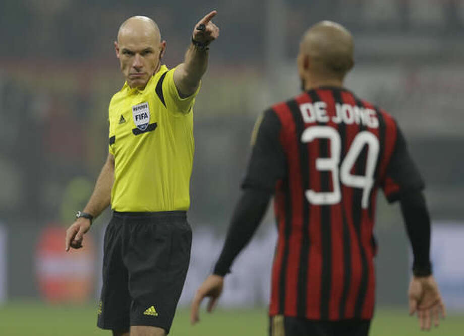 FILE - In this Wednesday, Dec.11, 2013 file photo, referee Howard Webb gestures to AC Milan midfielder Nigel de Jong during a Champions League, Group H, soccer match between AC Milan and Ajax at the San Siro stadium, in Milan, Italy. Moments before the start of the most game of his life, Webb had been struck down by another bout of Obsessive compulsive disorder, a condition in which a person has obsessive thoughts and compulsive behavior. Webb kept the condition secret throughout a career that saw him referee the Champions League final and World Cup final in the same year, 2010, fearing the harsh world of soccer would mark him down as mentally unsound. (AP Photo/Luca Bruno, file)