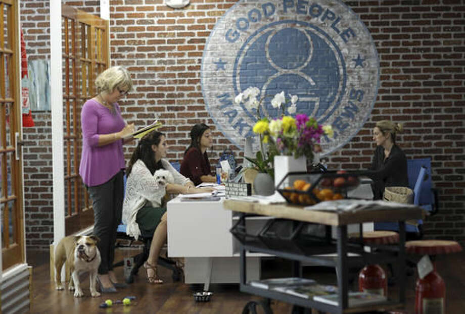 In this Tuesday, Oct. 18, 2016, photo, Barbara Goldberg, CEO of O'Connell & Goldberg Public Relations, left, consults with her staff with her bulldog Rosie at her side, at her office in Hollywood, Fla. Goldberg is a small business owner who believes pets improve the quality of their work life, boosting morale and easing tension for staffers. (AP Photo/Lynne Sladky)