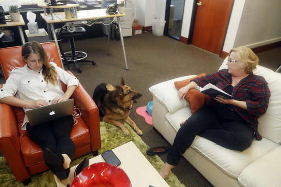 In this Monday, Oct. 17, 2016, photo, Marianne O'Connor, at right, CEO of Sterling Communications, talks to her dog Kaia, center, next to employee Sarah Koniniec, at the company's office, in Los Gatos, Calif. Many small business owners believe pets improve the quality of work life. (AP Photo/Marcio Jose Sanchez)