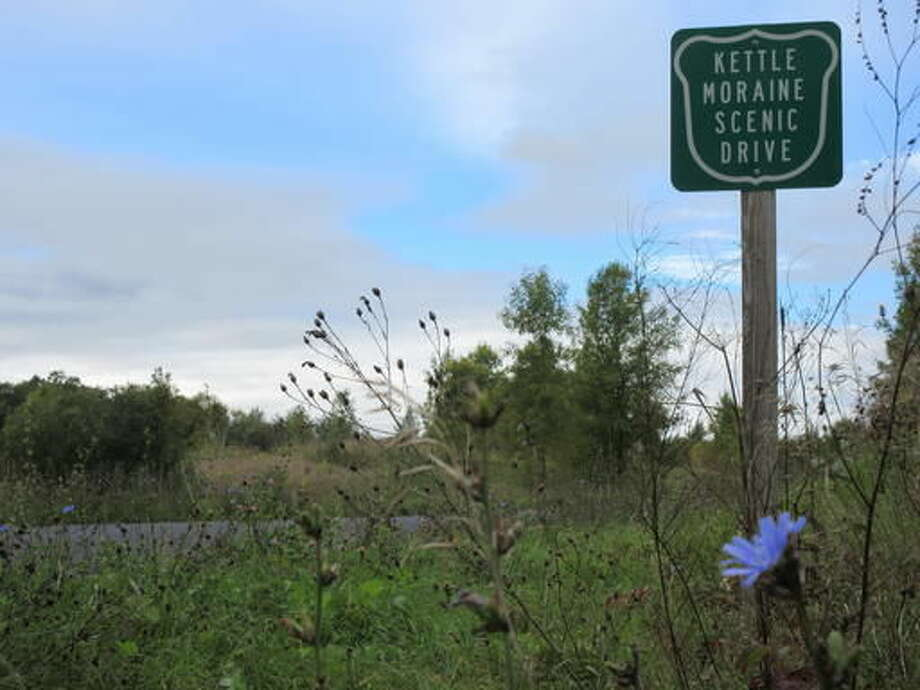 This Sept. 27, 2016 photo shows wildlflowers growing near a sign for the Kettle Moraine Scenic Drive in Wisconsin, in the northern unit area for the Kettle Moraine State Forest. The Kettle Moraine is a geological formation created thousands of years ago by the movement of glaciers. Today visitors can follow the Kettle Moraine Scenic Drive through rural farming areas and rustic woodlands, and hike a variety of trails to experience landscapes that range from prairie to wetlands to forests. (AP Photo/Beth J. Harpaz)