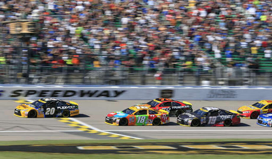 NASCAR driver Matt Kenseth (20) leads competitors onto the first lap of a Sprint Cup series auto race at Kansas Speedway in Kansas City, Kan., Sunday, Oct. 16, 2016. Sprint Cup Series drivers Kyle Busch (18), Martin Truex Jr. (78) and Carl Edwards (19) follow Kenseth. (AP Photo/Orlin Wagner)