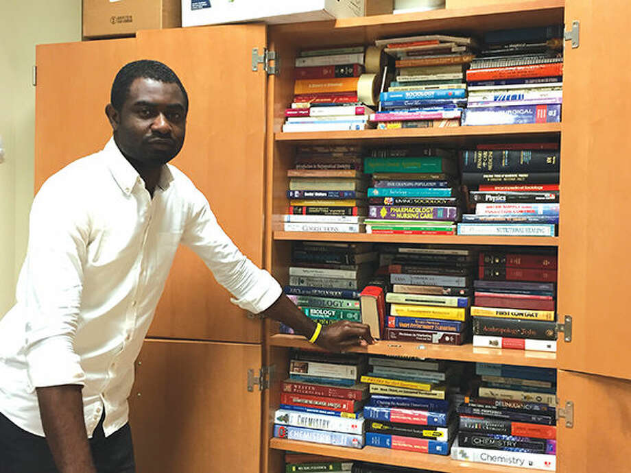 SIUE graduate student Philip Alabi with some of the more than 900 books he hopes to ship back for use in Nigeria.