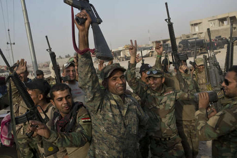 FILE -- In this Wednesday, Oct. 19, 2016 file photo, Iraqi army soldiers raise their weapons in celebration on the outskirts of Qayyarah, Iraq. In the week since Iraq launched an operation to retake Mosul from the Islamic State group, its forces have pushed toward the city from the north, east and south, battling the militants in a belt of mostly uninhabited towns and villages. In the heavily mined approaches to the city they met with fierce resistance, as IS unleashed suicide truck bombs, rockets and mortars. (AP Photo/Marko Drobnjakovic, File)