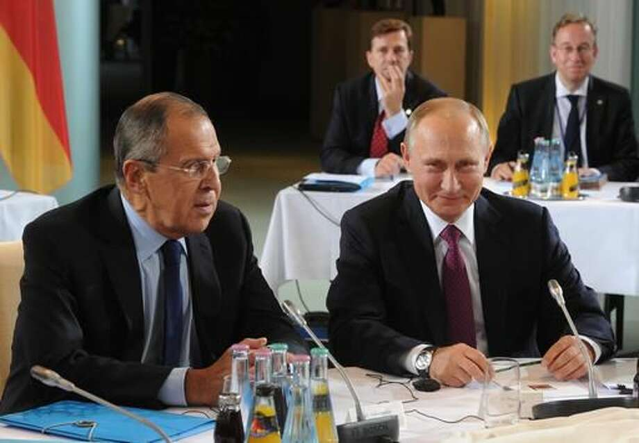 Russian President Vladimir Putin, right, and Russian Foreign Minister Sergey Lavrov, left, attend the talks at a summit with the leaders of Russia, Ukraine and France at the chancellery in Berlin, Germany, Wednesday, Oct. 19, 2016.(Mikhail Klimentyev/Pool Photo via AP)