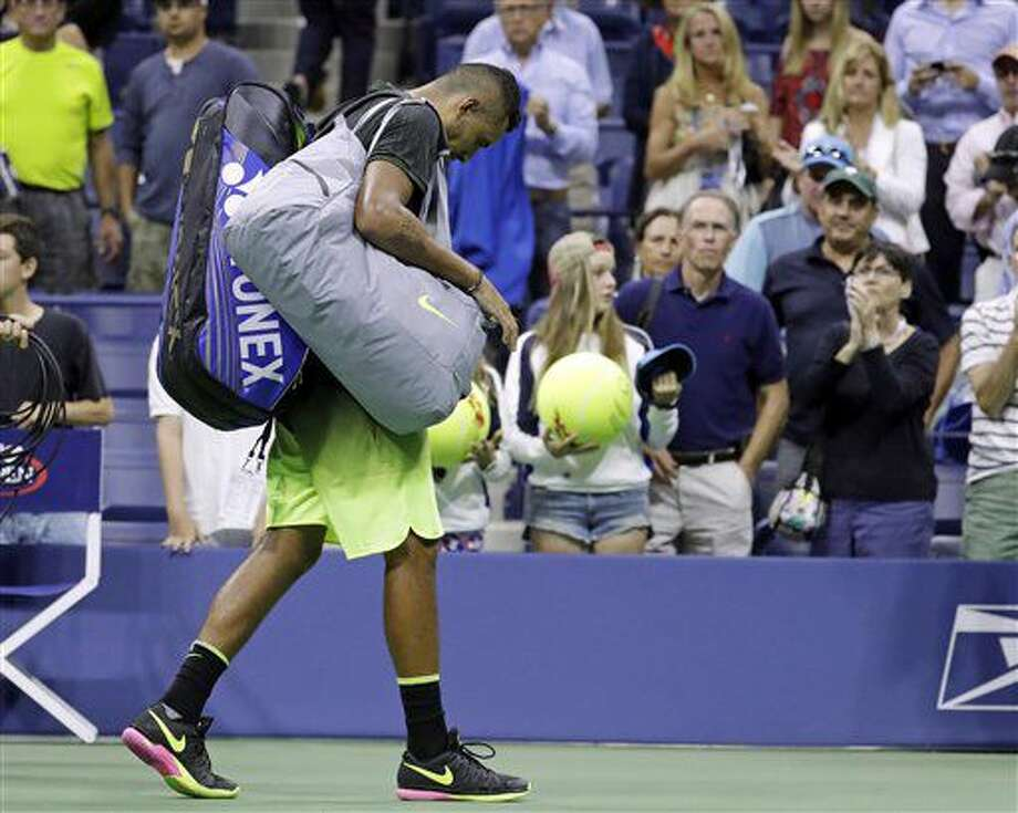 FILE - In this Saturday, Sept. 3, 2016 file photo Nick Kyrgios, of Australia, leaves the court after retiring from a match against Illya Marchenko, of Ukraine, during the U.S. Open tennis tournament, in New York. The ATP has suspended Nick Kyrgios for at least 3 weeks and fined him extra $25,000 for conduct contrary to 'integrity' of tennis. (AP Photo/Julio Cortez, File)