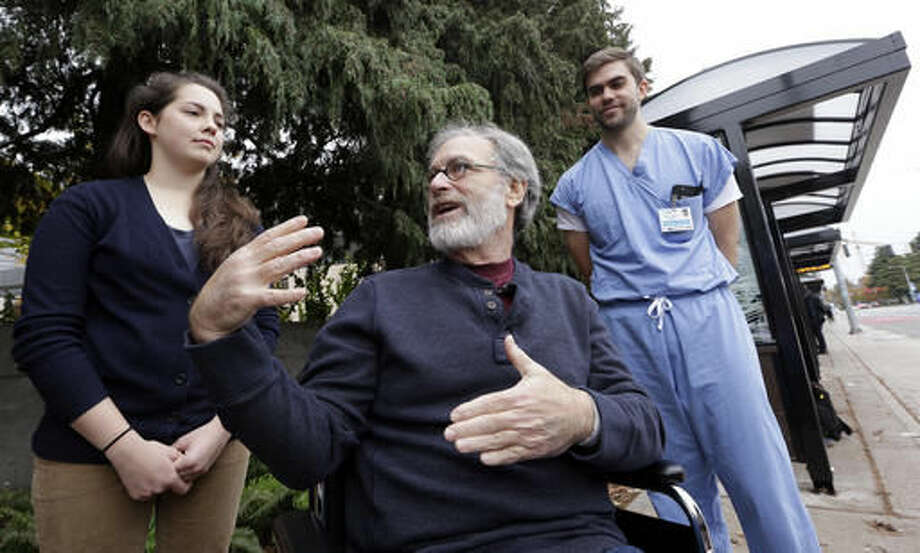 Stephen DeMont, center, sits in a wheelchair at the bus stop where he says that Zach Forcade, right, and Madeline Dahl saved his life days earlier in front of the University of Washington Medical Center, Wednesday, Oct. 19, 2016, in Seattle. When DeMont collapsed at a bus stop in front of the UW Medical Center on his morning commute, Dahl was one of 41 people within a 330-yard radius who happened to have a cell phone app alerting them to the emergency. Forcade, a medical student, witnessed the collapse and rushed over to begin chest compressions, as within moments Dahl, a cardiac nurse just getting off her shift in the hospital, was alerted by her phone and sprinted down the sidewalk, assisting until paramedics arrived. (AP Photo/Elaine Thompson)