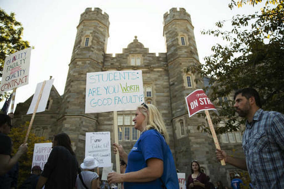 Faculty members Juliet Wunsch, center, and Jeremy Holmes, right, walk a picket line at West Chester University in West Chester, Pa., Wednesday, Oct. 19, 2016. Faculty at Pennsylvania state universities went on strike Wednesday morning after contract negotiations between the Pennsylvania State System of Higher Education and its faculty union hit an impasse. (AP Photo/Matt Rourke)
