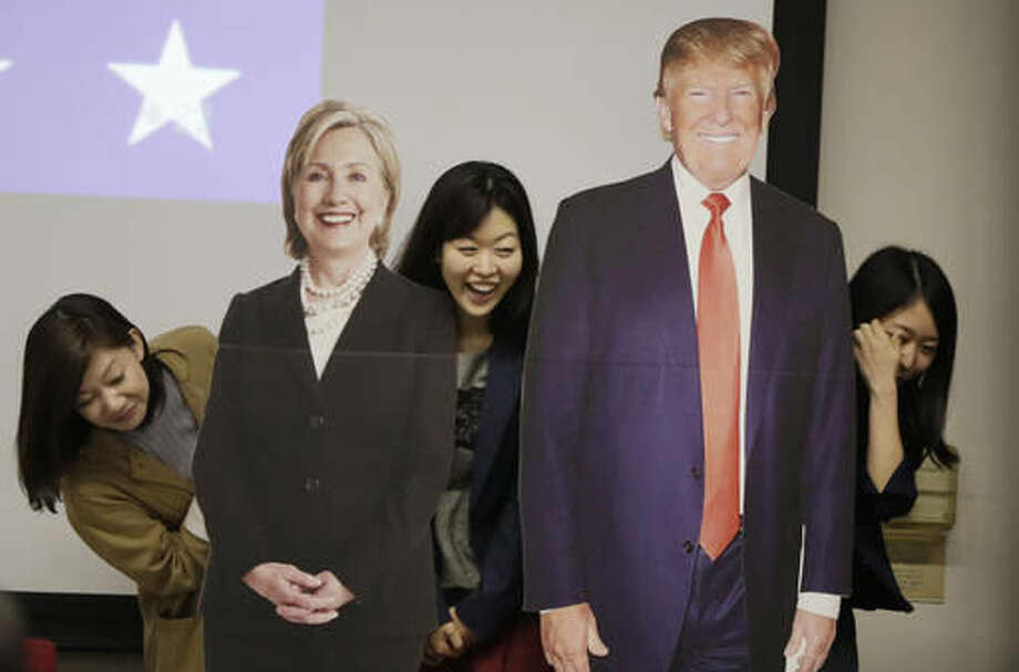 Guests pose for a photo with life-sized cutouts of Democratic presidential nominee Hillary Clinton and Republican presidential nominee Donald Trump prior to a public viewing of the U.S. presidential election debate between Clinton and Trump at the U.S. Embassy in Tokyo, Thursday, Oct. 20, 2016. (AP Photo/Eugene Hoshiko)