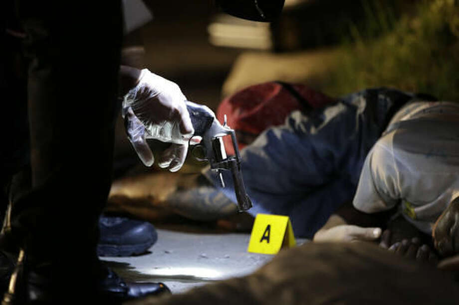 In this Sept. 6, 2016 photo, policemen check the gun recovered from one of two unidentified drug suspects after they were shot dead by police as they tried to evade a checkpoint in Quezon city, north of Manila, Philippines. Bodies had begun turning up in cities all over the Philippines ever since President Rodrigo Duterte launched a controversial war on drugs this year. Drug dealers and drug addicts, were being shot by police or slain by unidentified gunmen in mysterious, gangland-style murders that were taking place at night. (AP Photo/Aaron Favila)