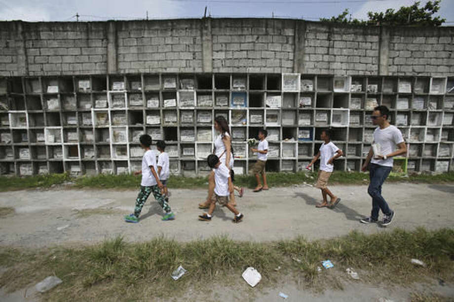 In this Sept. 14, 2016 photo, family and friends walk beside apartment-type tombs as they attend the funeral of alleged drug user Marcelo Salvador at a public cemetery in Las Pinas, south of Manila, Philippines. Drug dealers and drug addicts, were being shot by police or slain by unidentified gunmen in mysterious, gangland-style murders that were taking place at night. Salvador became a victim, the casualty of a vicious war on drugs that has claimed thousands of lives as part of a campaign by Philippine President Rodrigo Duterte. (AP Photo/Aaron Favila)