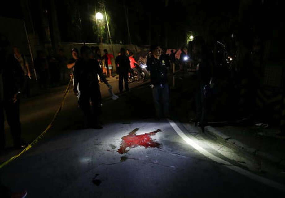 In this Sept. 5, 2016 photo, police inspect the site where alleged drug user Marcelo Salvador was shot dead by unidentified men in Las Pinas, south of Manila, Philippines. Drug dealers and drug addicts, were being shot by police or slain by unidentified gunmen in mysterious, gangland-style murders that were taking place at night. Salvador became a victim, the casualty of a vicious war on drugs that has claimed thousands of lives as part of a campaign by Philippine President Rodrigo Duterte. (AP Photo/Aaron Favila)