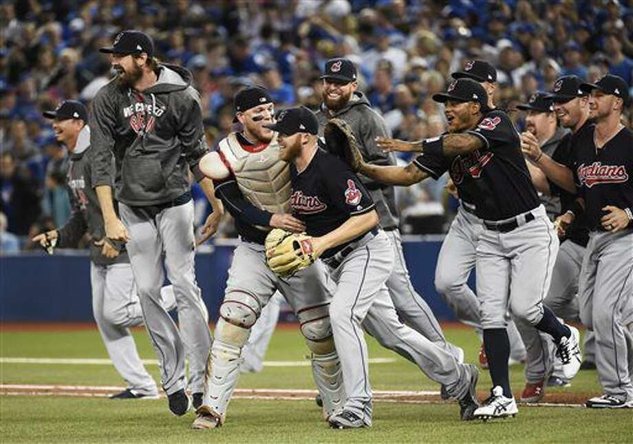 Cleveland Indians celebrate the team's 3-0 win over the Toronto Blue Jays in Game 5 of the baseball American League Championship Series in Toronto on Wednesday, Oct. 19, 2016. (Nathan Denette/The Canadian Press via AP)