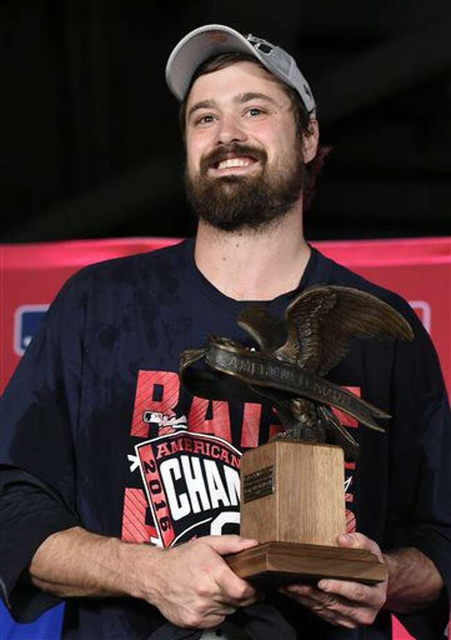 Cleveland Indians relief pitcher Andrew Miller accepts the MVP trophy for the series after the Indians defeated the Toronto Blue Jays 3-0 in Game 5 of the baseball American League Championship Series in Toronto on Wednesday, Oct. 19, 2016. (Nathan Denette/The Canadian Press via AP)