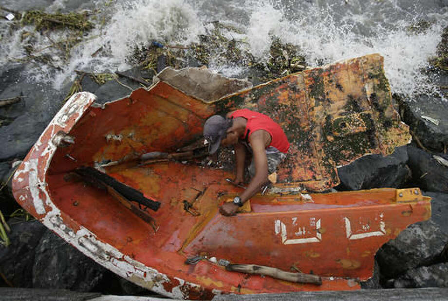 Filipino Joybin Marayo, 58, salvages metals on a damaged boat that was washed ashore by strong waves brought about by Typhoon Haima in Manila, Philippines on Thursday Oct. 20, 2016. Several people were killed after Super Typhoon Haima smashed into the northern Philippines with ferocious wind and rains overnight, flooding towns and forcing thousands to flee then weakening Thursday after slamming into a mountain range and blowing into the South China Sea, officials said. (AP Photo/Aaron Favila)