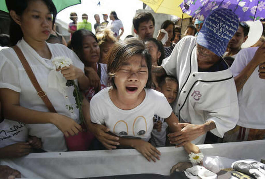 In this Sept. 12, 2016 photo, family and friends grieve as they pay their last respects to alleged drug user Robert Manuel Jr. during funeral rites at Manila's North Cemetery, Philippines. Manuel and two other men were killed by police during a buy-bust operation. Bodies had begun turning up in cities all over the Philippines ever since President Rodrigo Duterte launched a controversial war on drugs this year. Drug dealers and drug addicts, were being shot by police or slain by unidentified gunmen in mysterious, gangland-style murders that were taking place at night. (AP Photo/Aaron Favila)