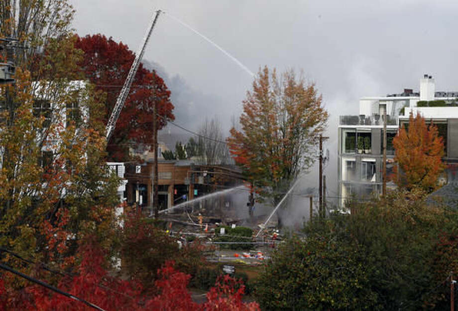 Smoke rises as firefighters battle a blaze after a gas explosion in Portland, Ore., Wednesday, Oct. 19, 2016. A powerful natural gas explosion that neighbors said felt like an earthquake rocked the busy injuring two firefighters and two civilians. One building in the popular shopping district was reduced to rubble and the exterior of one side of another building had been ripped off, its windows blown out. (AP Photo/Don Ryan)
