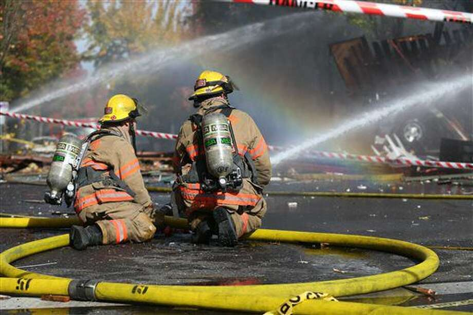 Firefighters hose down an area after a gas explosion, Wednesday, Oct. 19, 2016 in Portland, Ore. A powerful natural gas explosion that neighbors said felt like an earthquake rocked the busy a busy Portland, Oregon, shopping district and started a fire that sent a huge plume of smoke over the heart of the city. (Dave Killen/The Oregonian via AP)