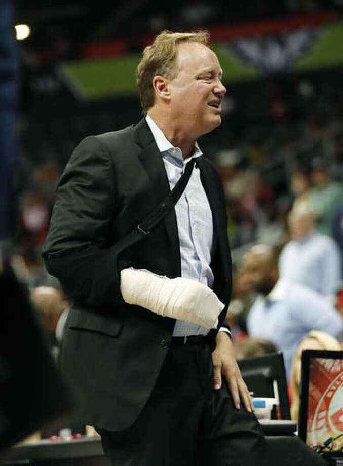 Atlanta Hawks coach Mike Budenholzer holds his leg and grimaces after he was run over on the sideline during the first half of the team's preseason NBA basketball game against the New Orleans Pelicans on Tuesday, Oct. 18, 2016, in Atlanta. Budenholzer, who was already nursing an injured hand, left the game. (AP Photo/John Bazemore)