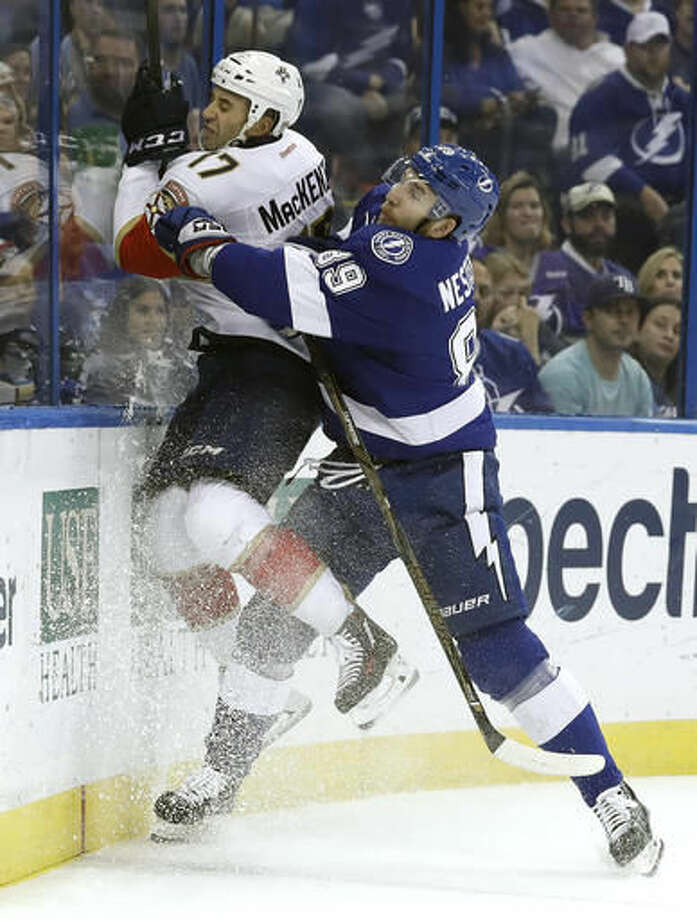 Tampa Bay Lightning defenseman Nikita Nesterov (89), of Russia, slams Florida Panthers center Derek MacKenzie (17) against the boards with a check during the first period of an NHL hockey game Tuesday, Oct. 18, 2016, in Tampa, Fla. (AP Photo/Chris O'Meara)
