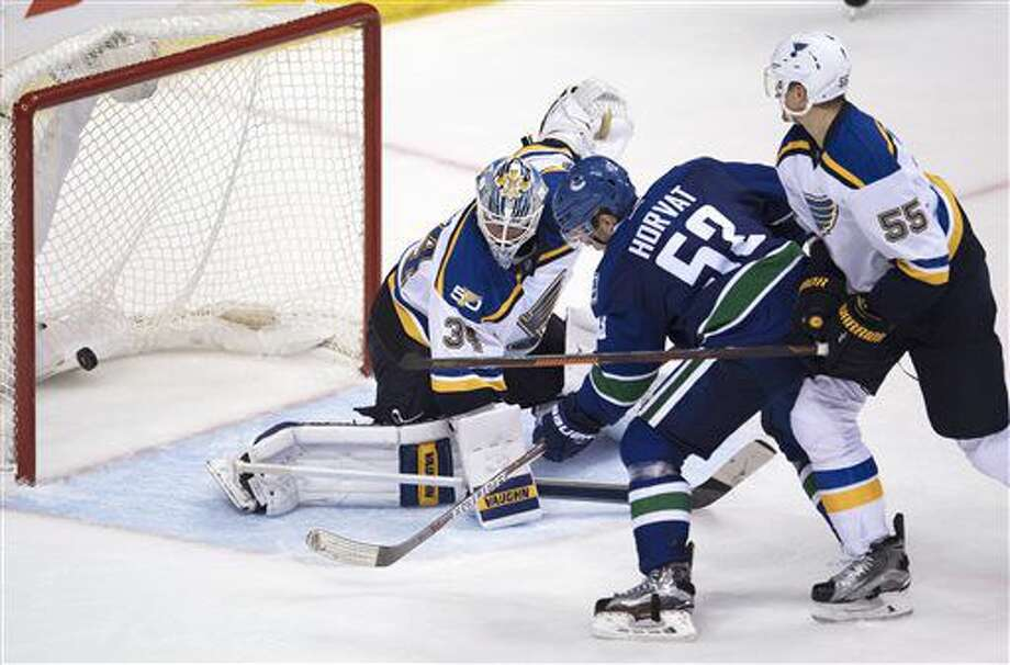 Vancouver Canucks centre Bo Horvat (53) sends a shot past St. Louis Blues goalie Jake Allen (34) as St. Louis Blues defenseman Colton Parayko (55) watches during the third period of an NHL hockey game Tuesday, Oct. 18, 2016, in Vancouver, British Columbia. (Jonathan Hayward/The Canadian Press via AP)