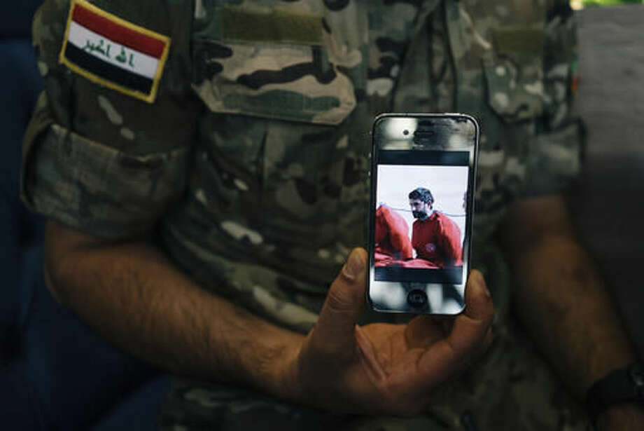 FILE - In this Aug. 10, 2016 file photo, Iraqi Army Cpl. Saif holds a phone displaying a screenshot from a video released by the Islamic State group that shows his brother, in Irbil, Iraq. He claims the video showed his brother's execution. Just over two years ago, Saif was holed up in a corner of Mosul's Nineveh hotel as he first began hearing rumors that his senior officers were fleeing the militant group's advance. Now, he's among the Iraqi forces beginning a massive operation to retake the country's second city from the militants.(AP Photo/Alice Martins, File)