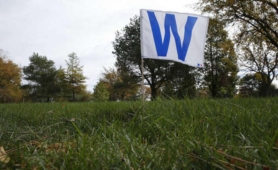 A Cubs W flag marks the final resting place of William F. Simon, a noted husband, dad, grandpa, on his grave stone at the All Saints Cemetery Wednesday, Oct. 19, 2016, in Des Plaines, Ill. In a city where fans have been known to scatter ashes of the dearly departed at Wrigley Field, families of those who could no longer wait 'till next season are planting Cubs pennants and flags at the graves of loved ones or sending them off to the great beyond with Cubs hats and jerseys in their caskets. (AP Photo/Charles Rex Arbogast)