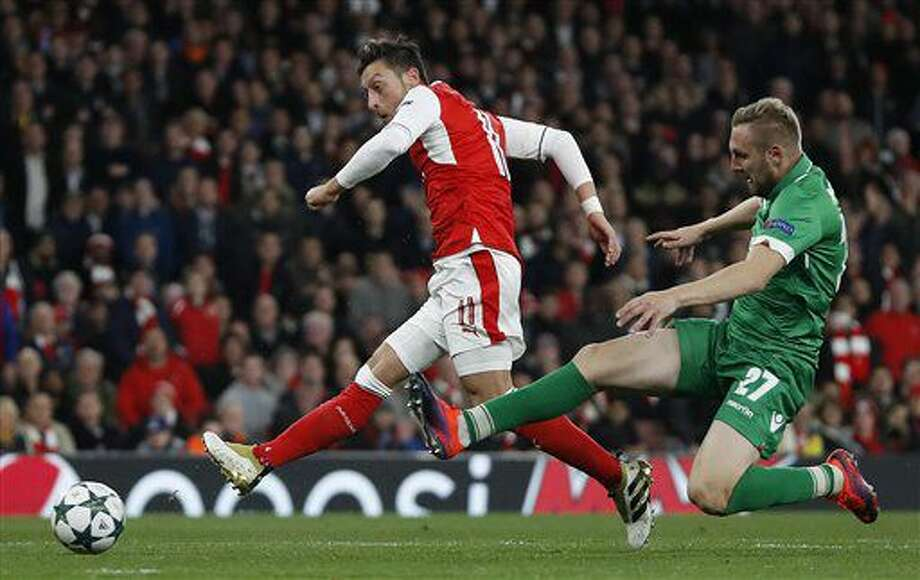 Arsenal's Mesut Ozil, left, scores during the Champions League Group A soccer match between Arsenal and Ludogorets Razgrad at Emirates stadium in London Wednesday, Oct. 19, 2016. (AP Photo/Kirsty Wigglesworth)