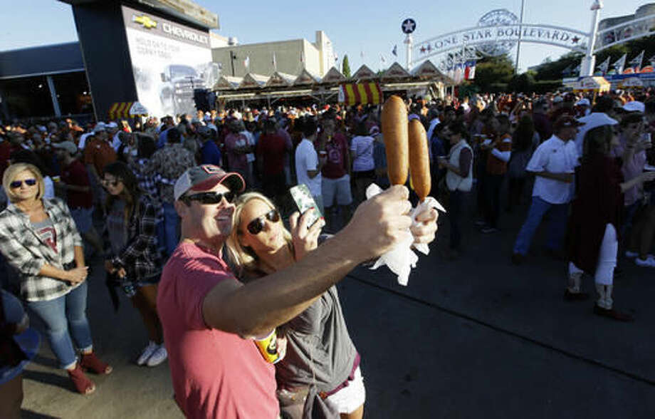 FILE - In this Oct. 8, 2016, file photo, Gwin Huey, right, and her husband, Ryan Huey, make a photo of their corn dogs at the state fair before an NCAA college football game between Texas and Oklahoma in Dallas.Now that the Big 12 has decided to stay at 10 schools, it's time to figure out whether or not to split up _ into football divisions. If so, how will the teams be divided? The league, which will keep its round-robin schedule, has to determine who will play in its championship game that returns next season. (AP Photo/LM Otero, File)