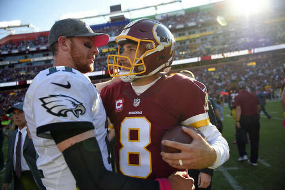 Philadelphia Eagles quarterback Carson Wentz, left, chats with Washington Redskins quarterback Kirk Cousins after an NFL football game, Sunday, Oct. 16, 2016, in Landover, Md. Washington won 27-20. (AP Photo/Nick Wass)