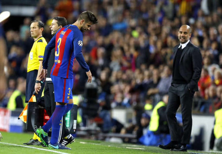 Manchester City's manager Pep Guardiola, right, watches as Barcelona's Gerard Pique leaves the pitch after injuring himself during a Champions League, Group C soccer match between Barcelona and Manchester City, at the Camp Nou stadium in Barcelona, Wednesday, Oct. 19, 2016. (AP Photo/Francisco Seco)