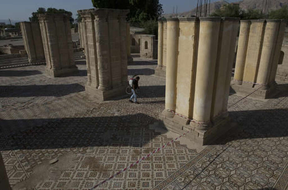 A laborer from the Palestinian Ministry of Tourism and Antiquities works at the site of a 7th century, 827 square meter (8900 square ft) mosaic ahead of the opening ceremony at the Islamic archaeological site of Hisham Palace, in the West Bank city of Jericho, Thursday, Oct. 20, 2016. The unique mosaic was displayed for the first time in its entirety to the public Thursday before it undergoes a US $13 million Japanese funded project to protect it and exhibit it to visitors. (AP Photo/Nasser Nasser)