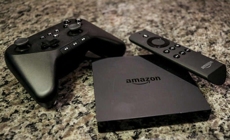 FILE - This Sept. 29, 2014, file photo, shows the Amazon Fire TV, a product for streaming popular video services, apps and games in high-definition, in Decatur, Ga. Amazon's Fire TV streaming devices will no longer emphasize video from its own store. Software updates coming in 2016 will give movies and TV shows from Netflix, HBO and other competitors equal prominence on the devices' home screen. The approach is similar to one Apple took when it refreshed its Apple TV device in 2015. (AP Photo/Ron Harris, File)
