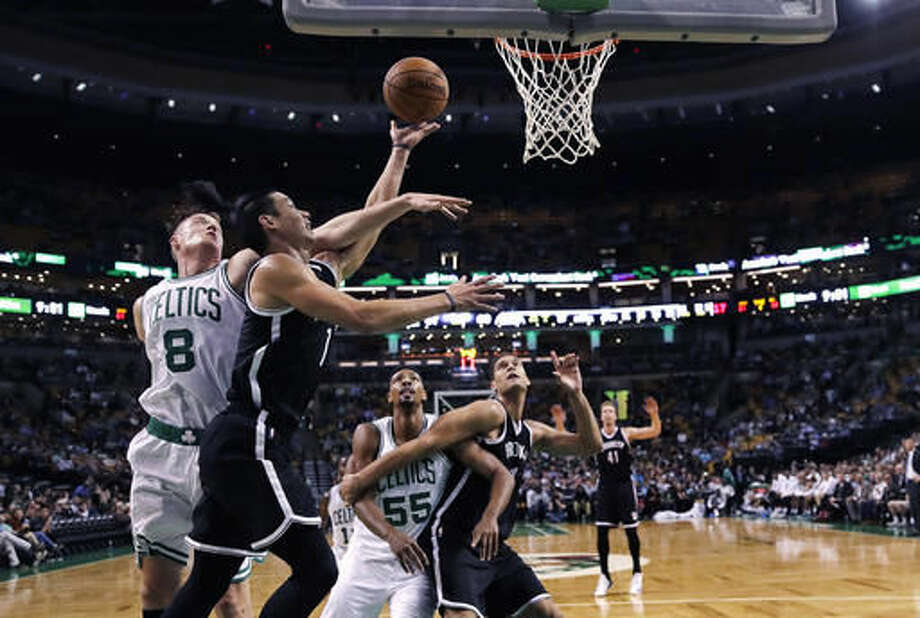 Boston Celtics forward Jonas Jerebko, of Sweden, (8) tries to block Brooklyn Nets guard Jeremy Lin on a drive to the basket during the second half of a preseason NBA basketball game in Boston, Monday, Oct. 17, 2016. The Celtics defeated the Nets 120-99. (AP Photo/Charles Krupa)