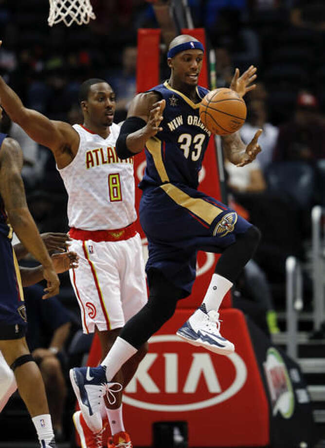 New Orleans Pelicans forward Dante Cunningham (33) passes the ball as Atlanta Hawks center Dwight Howard (8) defends during the first half of a preseason NBA basketball game Tuesday, Oct. 18, 2016, in Atlanta. (AP Photo/John Bazemore)