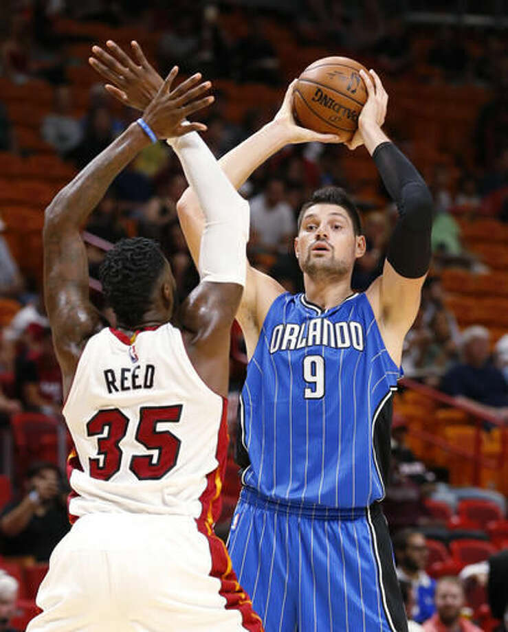 Orlando Magic center Nikola Vucevic (9) looks for an open teammate past Miami Heat center Willie Reed (35) during the first half of an NBA preseason basketball game, Tuesday, Oct. 18, 2016, in Miami. (AP Photo/Wilfredo Lee)
