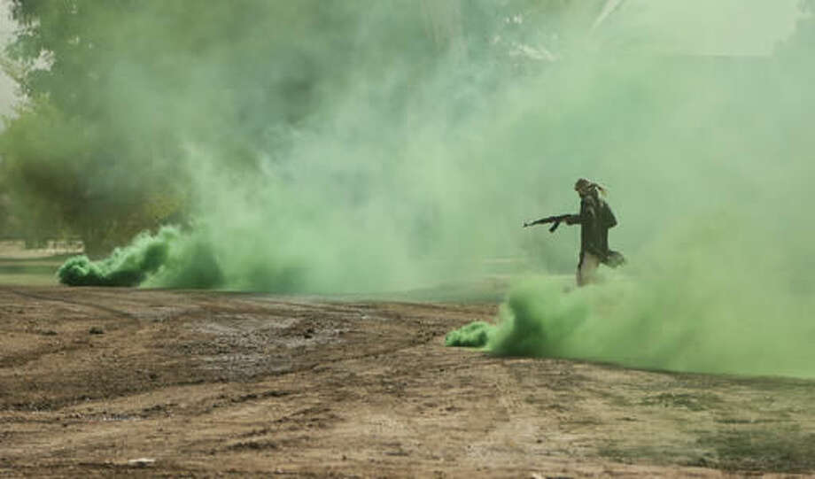 FILE - In this Saturday, Aug. 13, 2016 file photo, a soldier from the 1st Battalion of the Iraqi Special Operations Forces in the role of an Islamic State militant runs through green smoke during a training exercise to prepare for the operation to re-take Mosul from IS, in Baghdad, Iraq. Iraq's special forces, which barreled into a town east of Mosul on Thursday despite a wave of suicide attacks, are the country's most professional and least sectarian fighting force. Officially known as the Counter Terrorism Service, the troops have played a key role in wresting back towns and cities from IS, and are expected to lead the charge in Mosul. (AP Photo/Maya Alleruzzo, File)