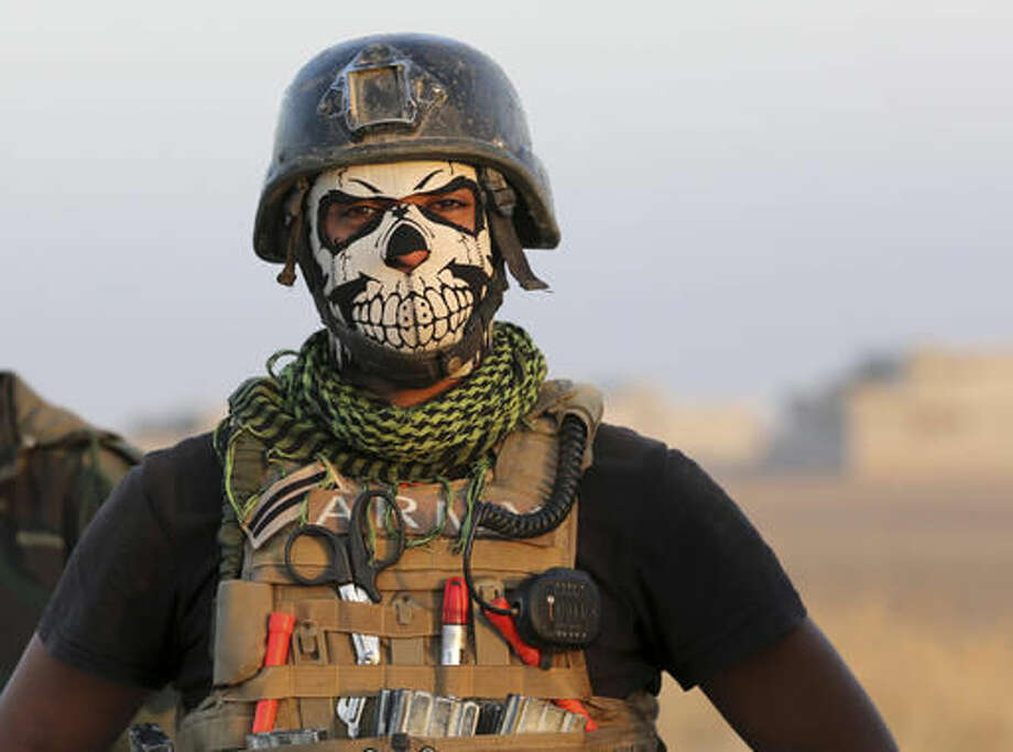 A member of Iraq's elite counterterrorism forces pauses as they advance towards the city of Mosul, Iraq, Thursday, Oct. 20, 2016. Iraq's special forces, which barreled into a town east of Mosul on Thursday despite a wave of suicide attacks, are the country's most professional and least sectarian fighting force. Officially known as the Counter Terrorism Service, the troops have played a key role in wresting back towns and cities from IS, and are expected to lead the charge in Mosul. (AP Photo/Khalid Mohammed)