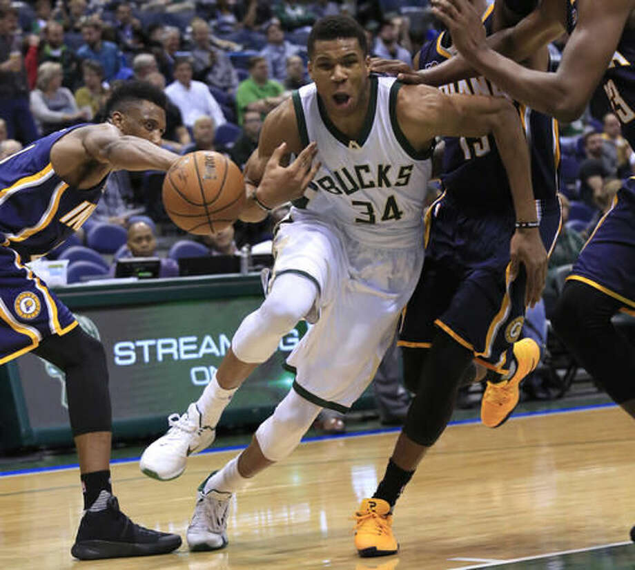 Milwaukee Bucks forward Giannis Antetokounmpo, center, loses the ball on a drive against the Indiana Pacers during the second half of an NBA preseason basketball game Wednesday, Oct. 19, 2016, in Milwaukee. (AP Photo/Darren Hauck)