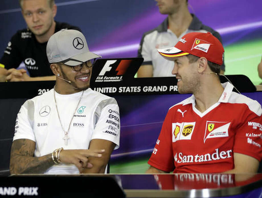 Mercedes driver Lewis Hamilton, left, of Britain, talks with Ferrari driver Sebastian Vettel, of Germany, during a news conference for the Formula One U.S. Grand Prix auto race at the Circuit of the Americas, Thursday, Oct. 20, 2016, in Austin, Texas. (AP Photo/Eric Gay)