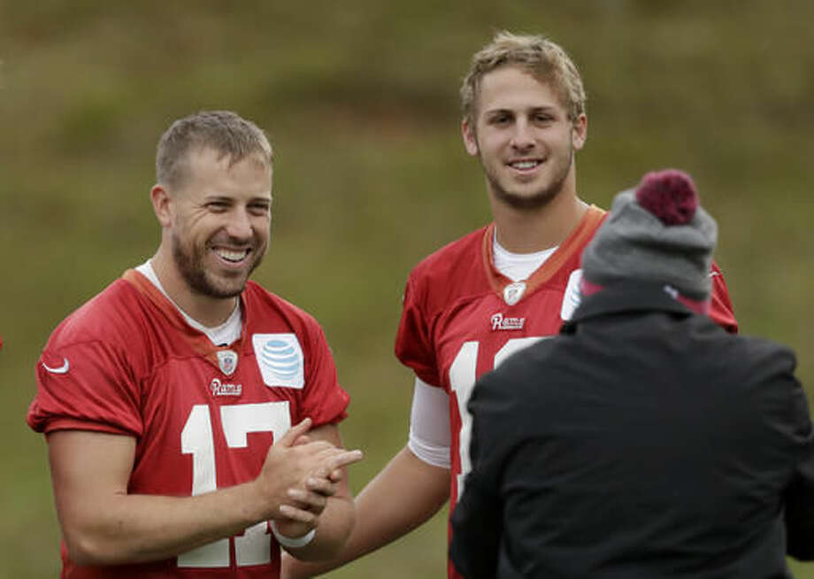 Los Angeles Rams quarterbacks Case Keenum, left, and Jared Goff pose for photographs together at the end of a practice session at Pennyhill Park Hotel in Bagshot, England, Thursday, Oct. 20, 2016. The Los Angeles Rams are due to play the New York Giants at Twickenham stadium in London on Sunday in a regular season NFL game. (AP Photo/Matt Dunham)