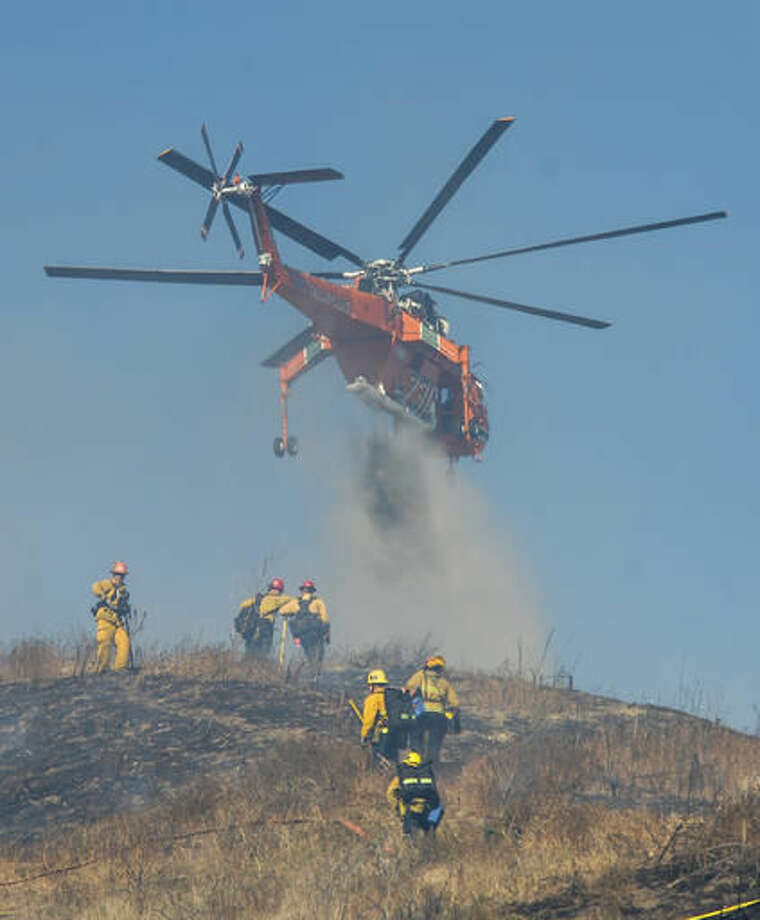Firefighters battle a brush fire on the ground and from the air on a wind driven fire that threatened homes in the area Wednesday, Oct. 19, 2016, in the Lake View Terrace area of Los Angeles. (David Crane/Los Angeles Daily News/SCNG via AP) /Los Angeles Daily News via AP)