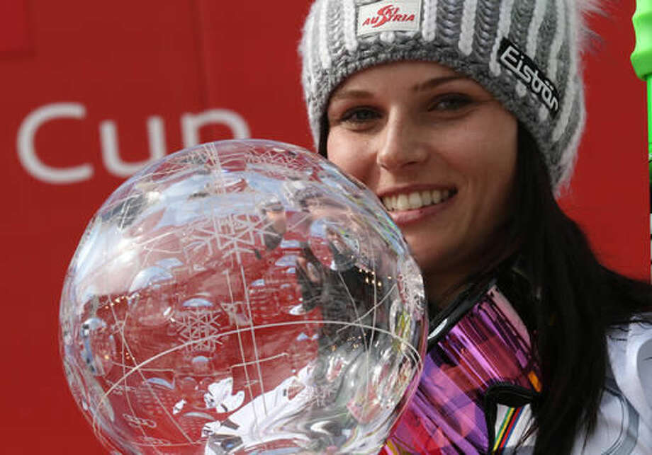 FILE - In this March 22, 2015 file photo then Anna Fenninger of Austria poses for photographers as she holds the alpine skiing women's World Cup overall trophy at the World Cup finals in Meribel, France. The first overall World Cup champion from Switzerland in more than two decades, Lara Gut starts her title defense as one of the favorites again when the season gets underway on Saturday, Oct. 22, 2016. As US athlete Lindsey Vonn has announced to compete in a reduced number of races and Anna Veith (former Anna Fenninger) has postponed her return from injury, American Mikaela Shiffrin could well become Gut's closest challenger. (AP Photo/Armando Trovati, File)
