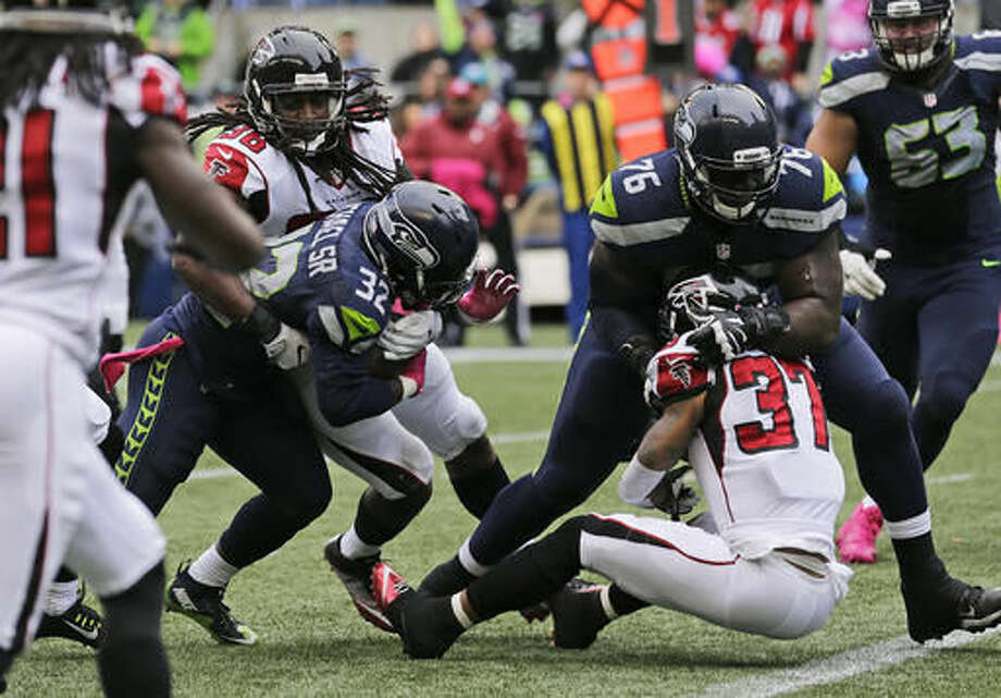 Seattle Seahawks running back Christine Michael (32) powers through a tackle attempt by Atlanta Falcons strong safety Kemal Ishmael, left, to score a touchdown in the first half of an NFL football game, Sunday, Oct. 16, 2016, in Seattle. (AP Photo/Stephen Brashear)