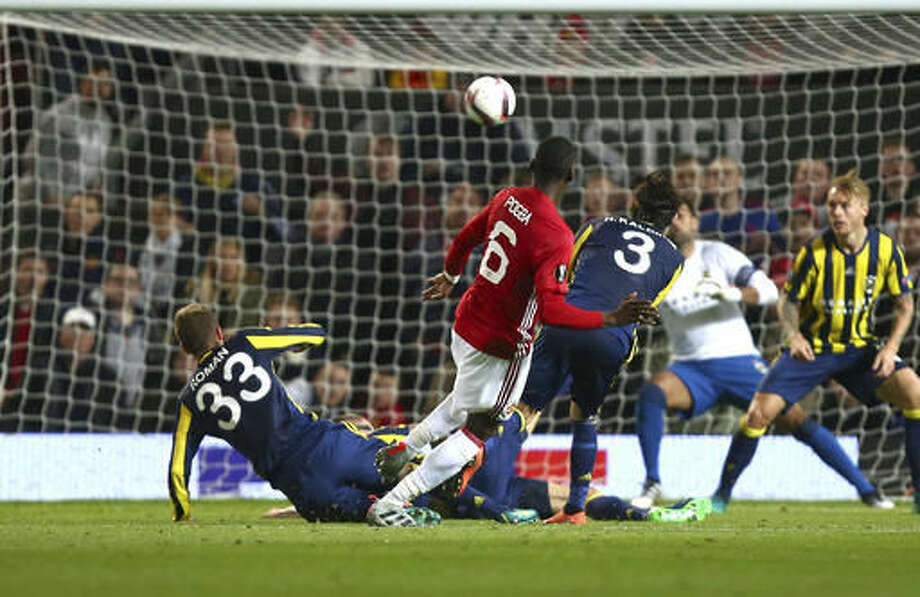 Manchester United's Paul Pogba, centre, scores his sides third goal during the Europa League Group A soccer match between Manchester United and Fenerbahce at Old Trafford stadium in Manchester, England, Thursday, Oct. 20, 2016. (AP Photo/Dave Thompson)